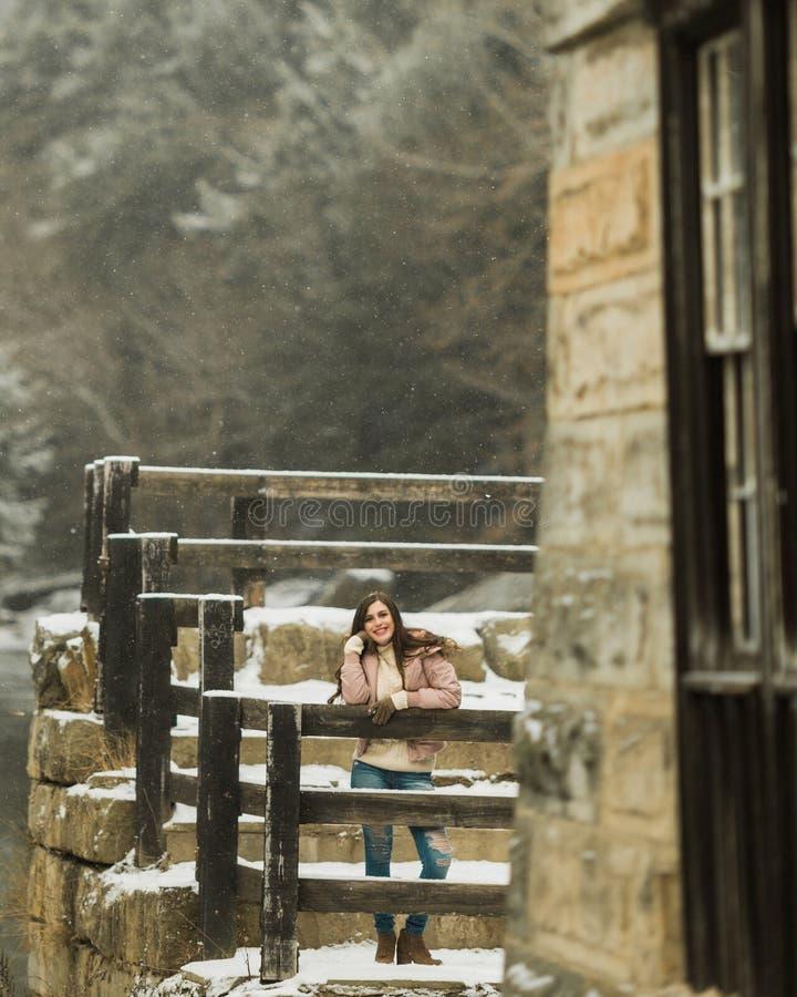 Tienermiddelbare schooloudste die in sneeuwvlagen glimlachen die de winterkleren buiten dragen stock foto's