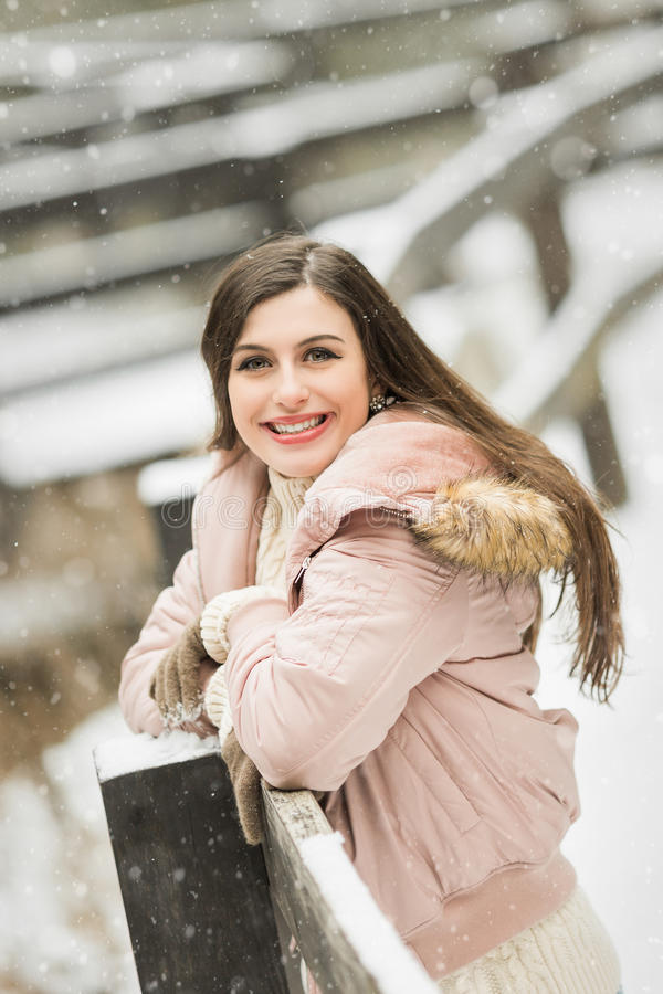 Tienermiddelbare schooloudste die in sneeuwvlagen glimlachen die de winterkleren buiten dragen stock afbeelding