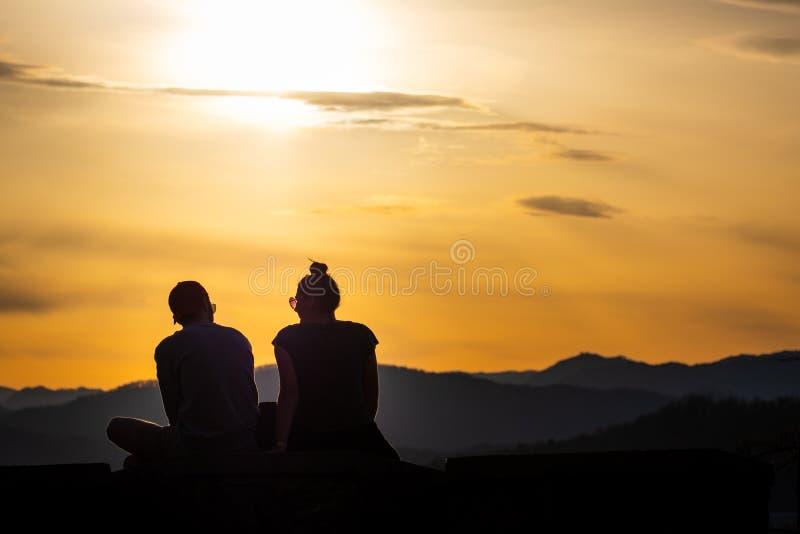 Tienerpaar die met zonnebril op heuvel zitten die van de zonsondergang genieten royalty-vrije stock foto