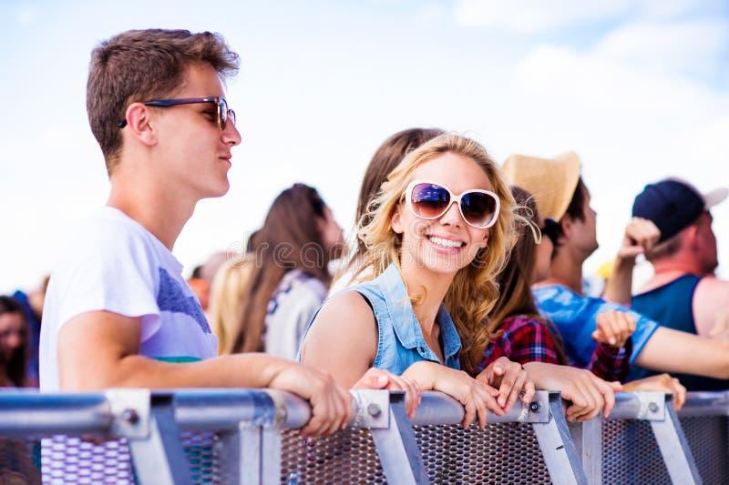 Tieners bij het festival van de de zomermuziek, bij de barrière stock foto
