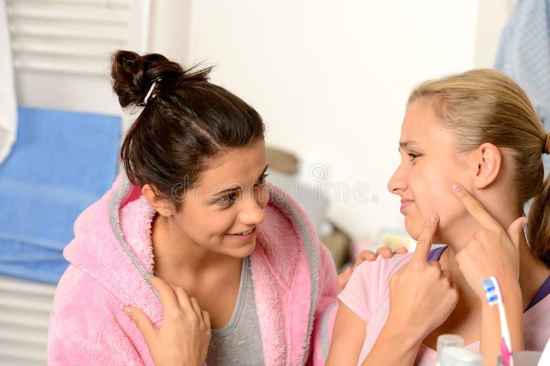 Tieners die acneproblemen in badkamers hebben stock fotografie