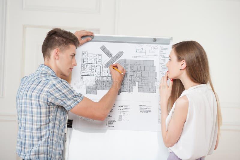 Tieners die bij projecterende tekening werken stock afbeeldingen