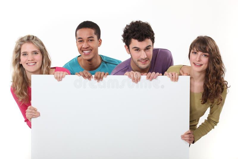 Tieners die een leeg teken steunen royalty-vrije stock afbeeldingen