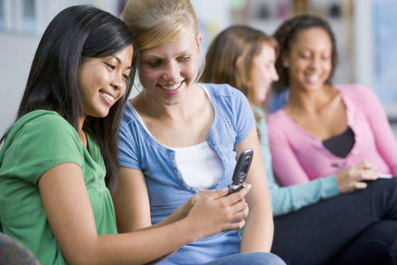 Tieners die een mobiele telefoon bekijken royalty-vrije stock afbeeldingen
