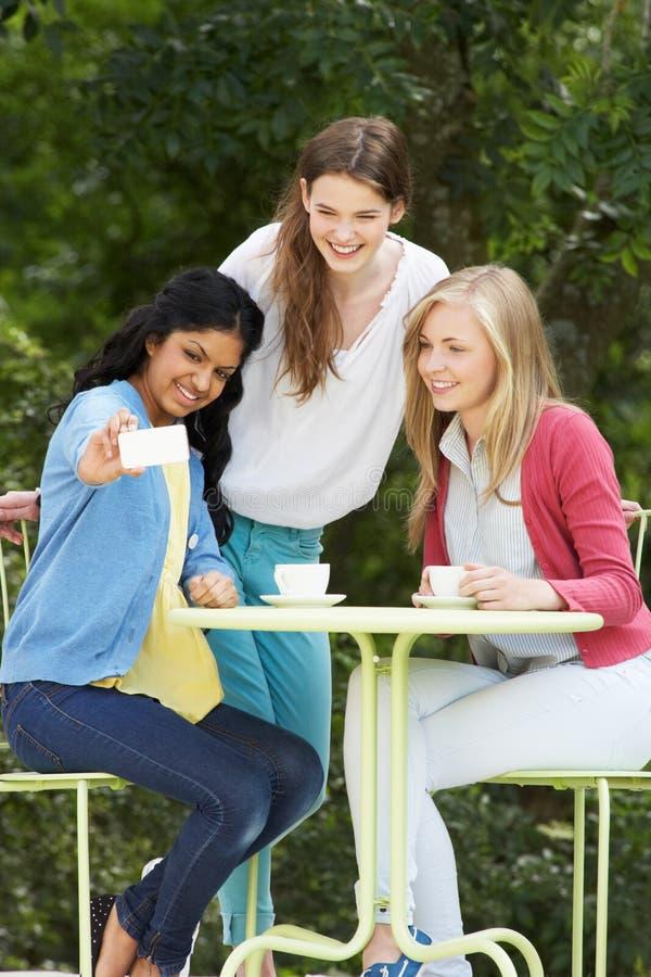 Tieners die Foto op Mobiele Telefoon nemen bij Openluchtkoffie stock afbeelding