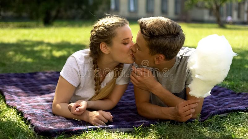 Tieners die, liggend op plaid in park, die gesponnen suiker, romantische datum houden kussen stock foto's