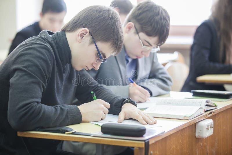 Tieners die nota's in hun oefenboeken maken stock foto
