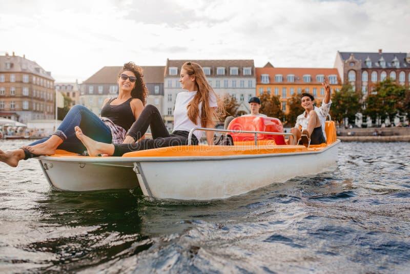 Tieners die op boot in het meer ontspannen royalty-vrije stock afbeelding