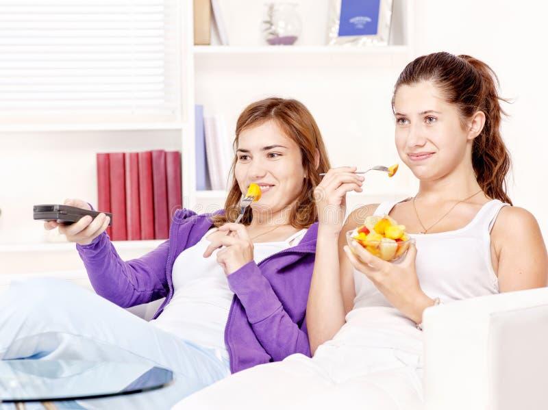 Tieners die op TV letten en fruitsalade eten stock foto