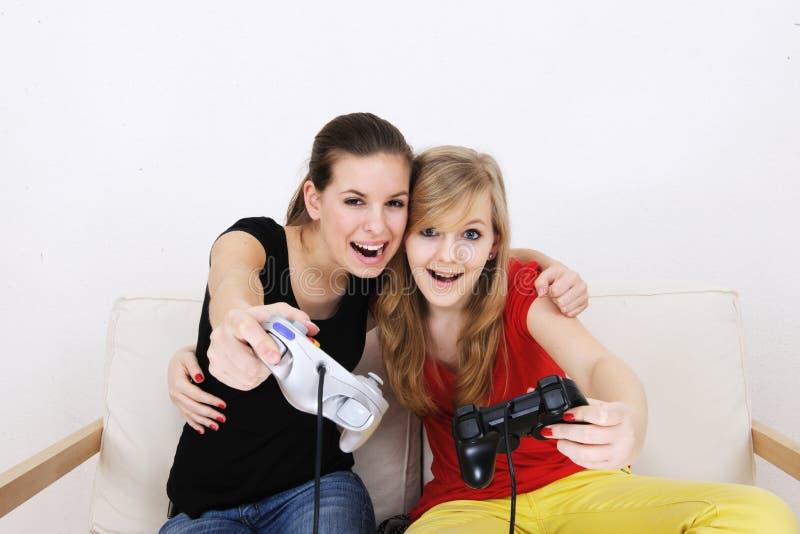 Tieners die pla van playstationteenagemeisjes spelen stock foto
