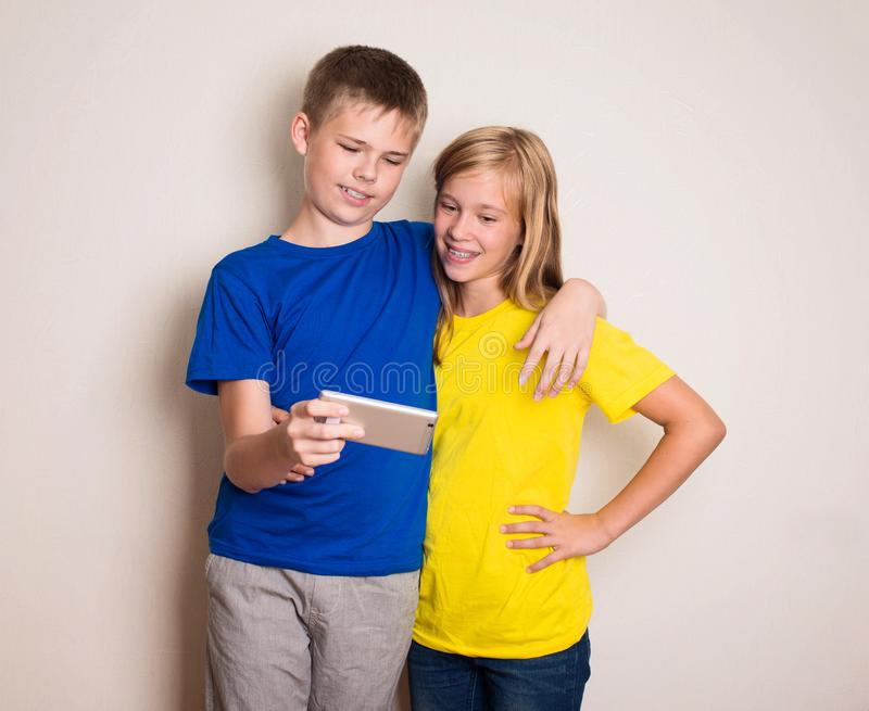 Tieners die pret met mobiele telefoons hebben Modern levensstijl en technologieconcept Kinderen die op foto of video op letten stock foto's