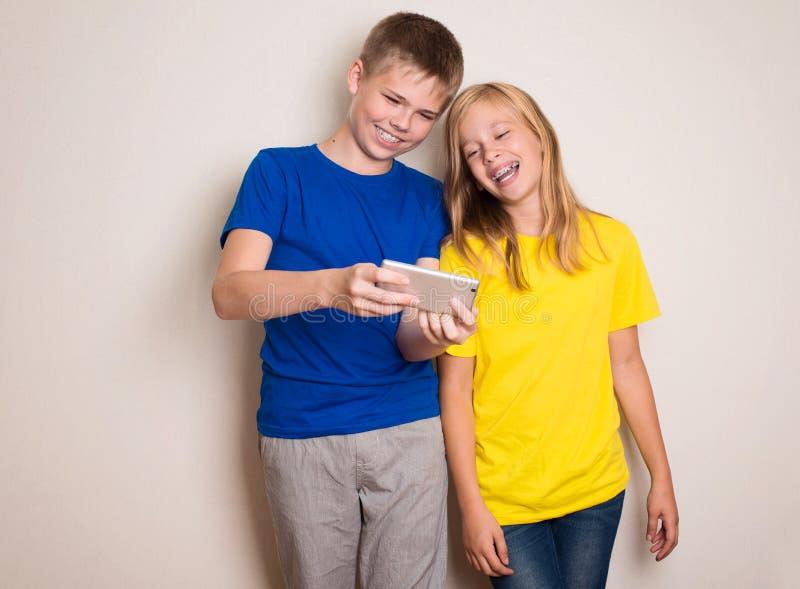 Tieners die pret met mobiele telefoons hebben Modern levensstijl en technologieconcept Kinderen die op foto of video op letten stock foto