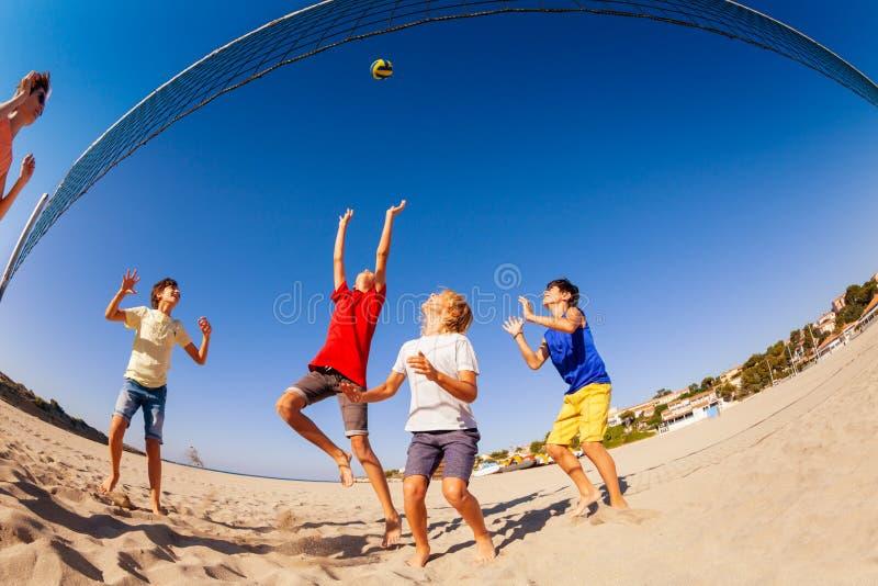 Tieners die strandvolleyball in de zomer spelen stock foto's