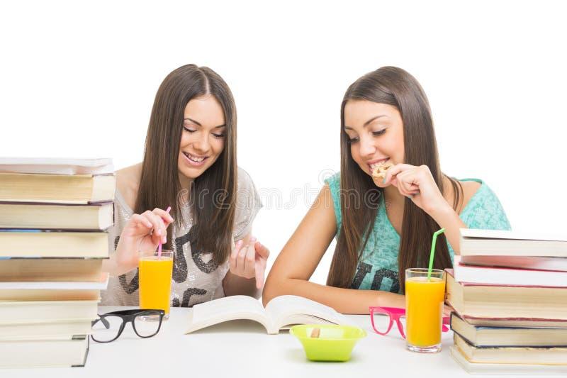 Tieners die terwijl samen het leren eten stock foto's