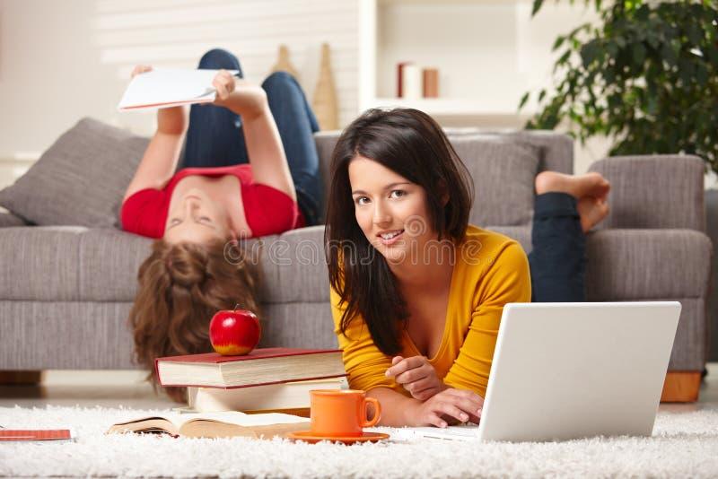 Tieners die thuis leren stock foto