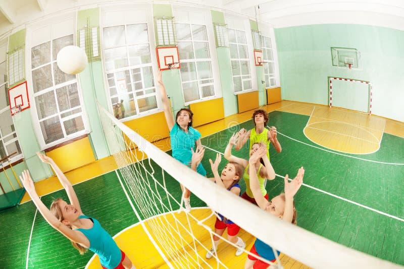 Tieners die volleyball in schoolgymnasium spelen royalty-vrije stock afbeelding