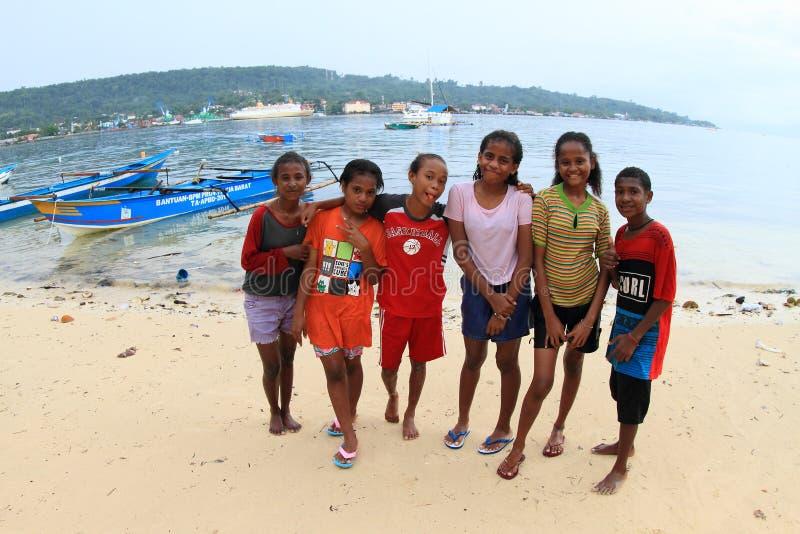 Tieners en jongen op strand in Manokwari stock foto's