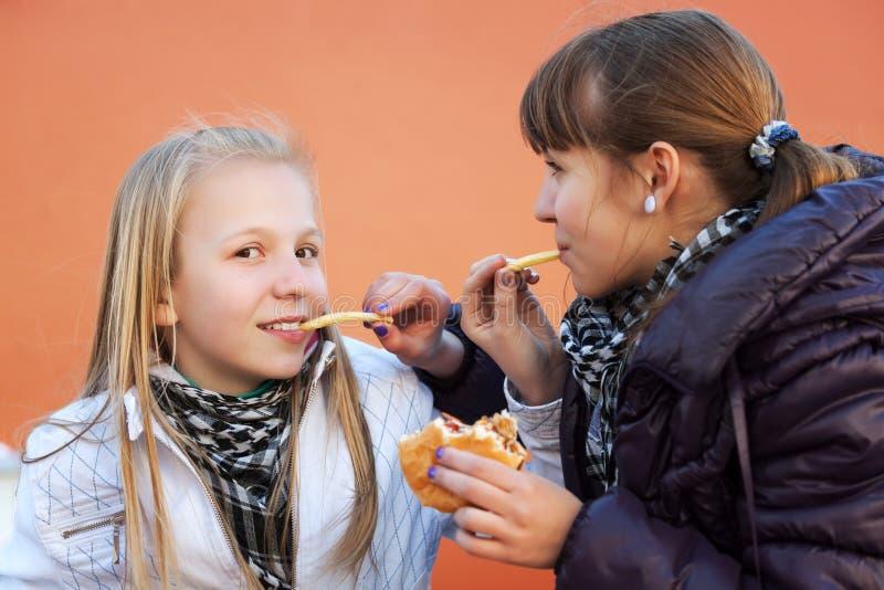 Tieners eten burgers royalty-vrije stock afbeelding