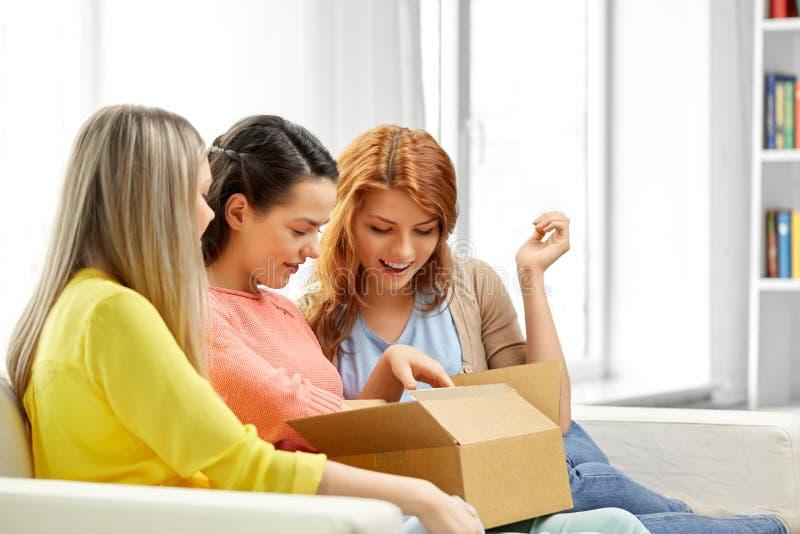 Tieners of vrienden die pakketdoos openen stock afbeeldingen