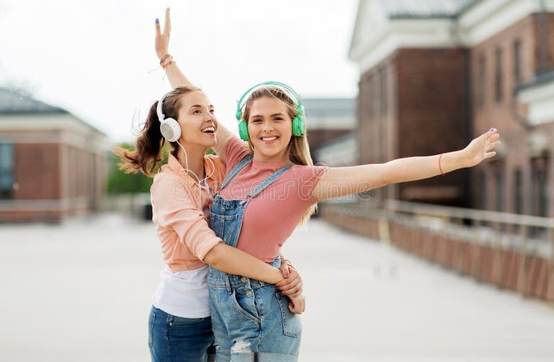 Tieners of vrienden in hoofdtelefoons in stad royalty-vrije stock afbeeldingen