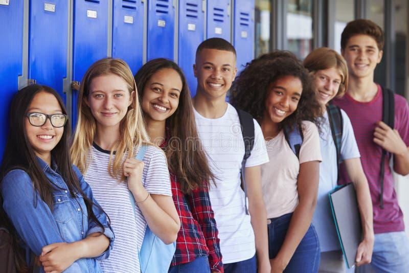 Tienerschooljonge geitjes die aan camera in schoolgang glimlachen stock foto's