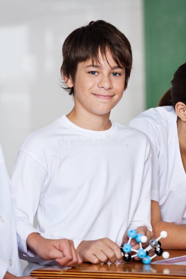 Tienerschooljongen met Moleculaire Structuur bij Bureau royalty-vrije stock afbeelding
