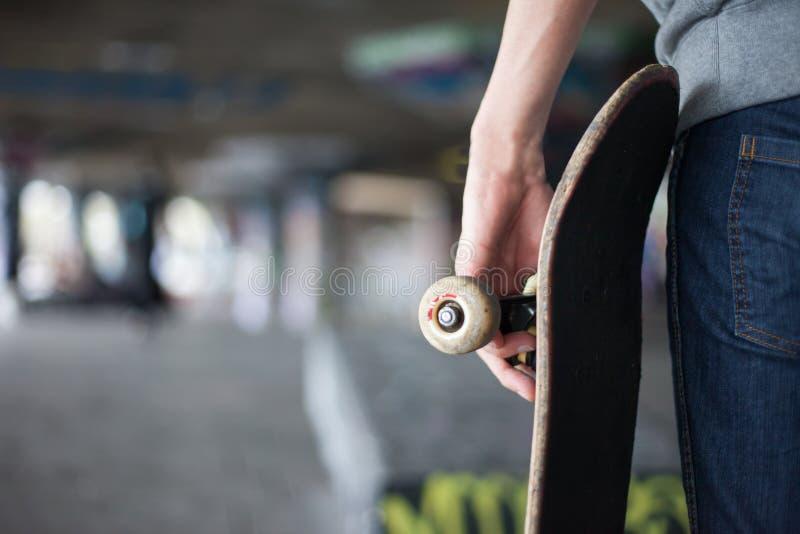 Tienerskateboarder met houding en raad stock afbeeldingen
