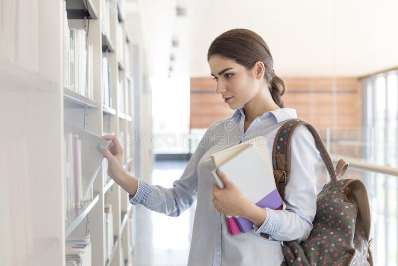 Tienerstudent die naar boek bij bibliotheek in universiteit zoeken stock afbeeldingen