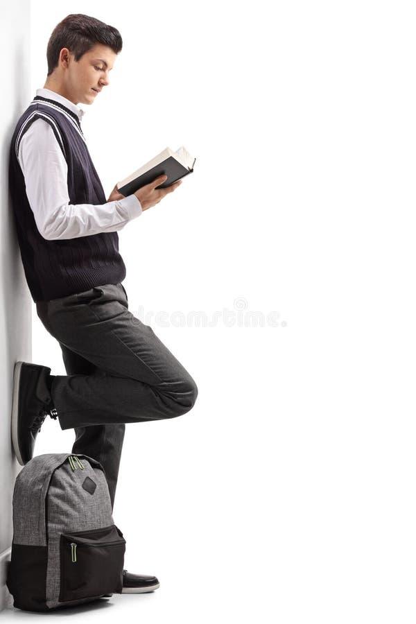 Tienerstudent die tegen een muur leunen en een boek lezen royalty-vrije stock fotografie