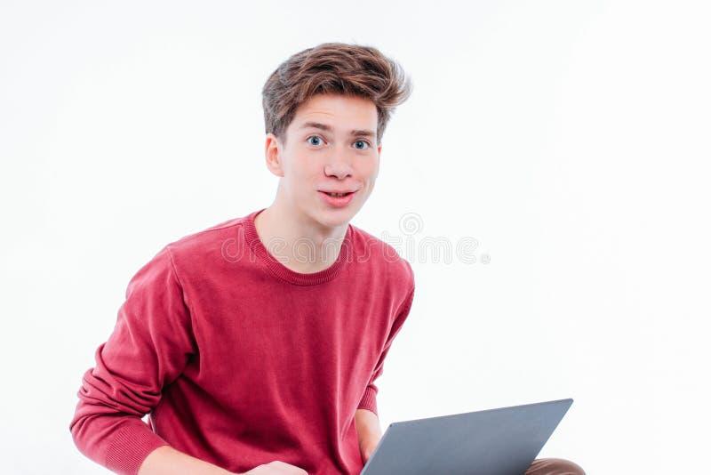 Tienerstudent met grappig gezicht die bij laptop aan witte achtergrond werken stock foto