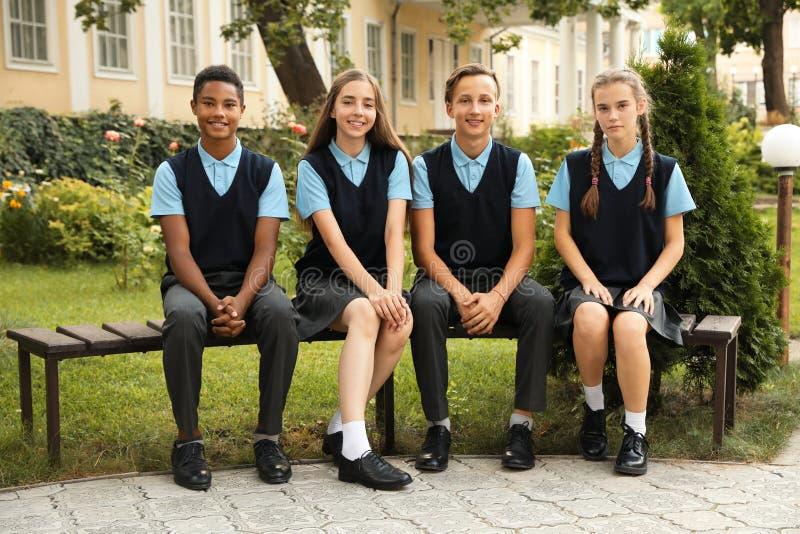 Tienerstudenten in modieuze school eenvormige zitting royalty-vrije stock afbeelding
