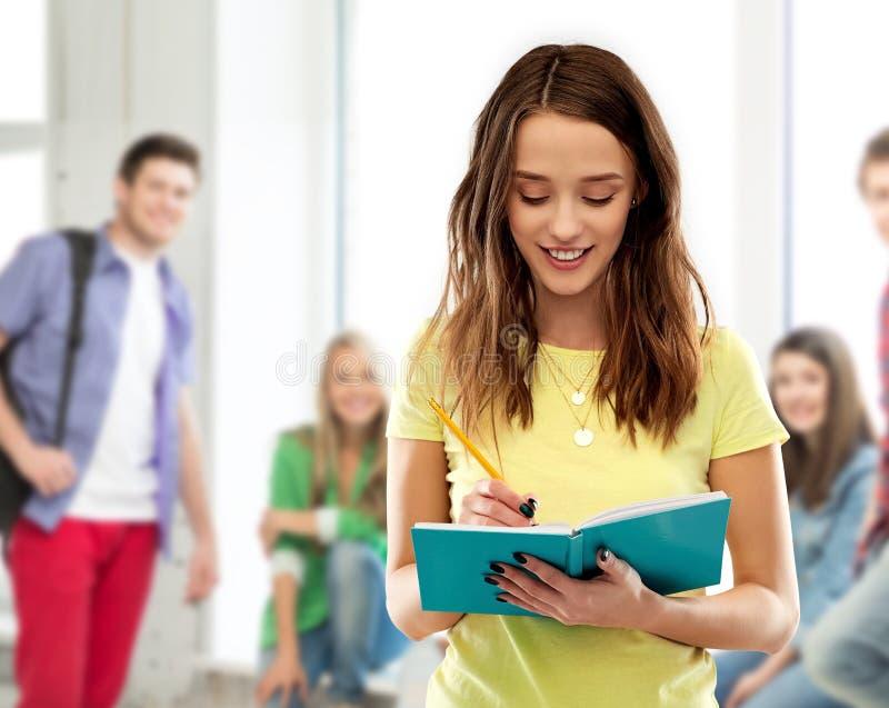 Tienerstudentenmeisje die aan agenda of notitieboekje schrijven royalty-vrije stock afbeelding