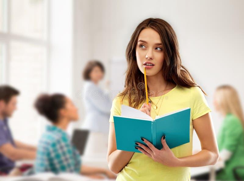 Tienerstudentenmeisje met notitieboekje op school stock foto's