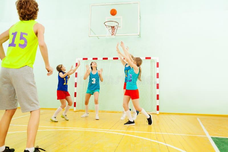 Tienerteam speelbasketbal in gymnastiek royalty-vrije stock afbeeldingen