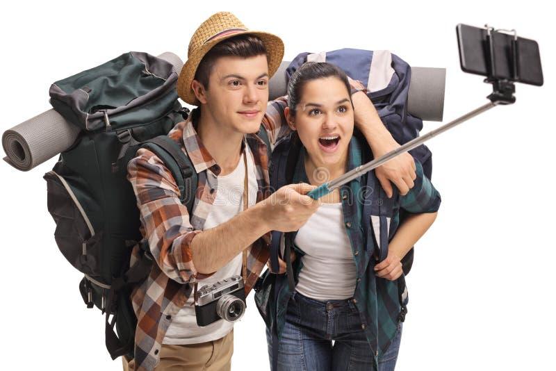 Tienertoeristen met rugzakken die een selfie met een stok nemen stock afbeeldingen