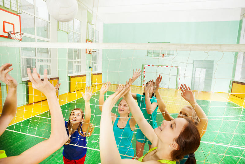 Tienervolleyballspelers in actie tijdens gelijke stock fotografie