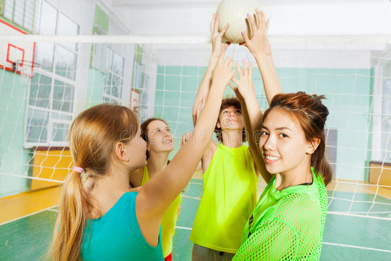 Tienervolleyballspelers met bal naast netto stock afbeelding