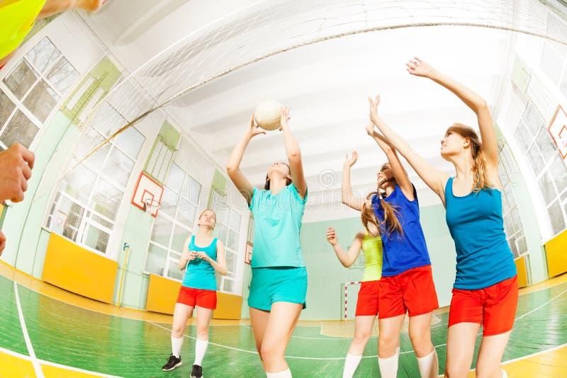 Tienervolleyballteam tijdens gelijke in gymnasium stock foto