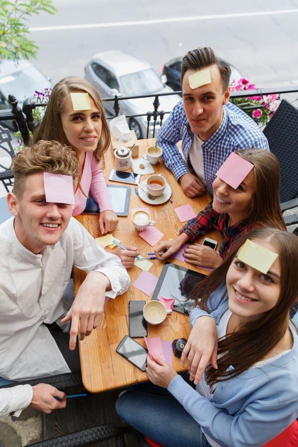 Tienervrienden die pret het spelen met stickers op voorhoofden op een koffieachtergrond hebben Het concept van de vriendenactivit stock afbeelding