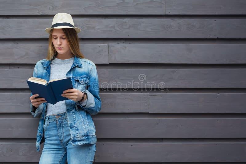 Tienervrouw gelezen boek buiten muur stock foto