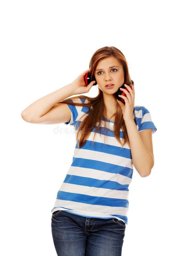 Tienervrouw met rode hoofdtelefoons stock afbeeldingen