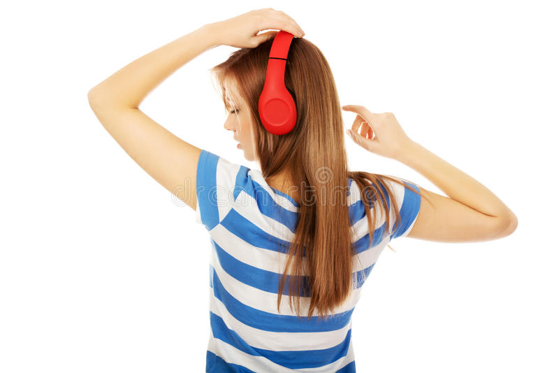 Tienervrouw met rode hoofdtelefoons royalty-vrije stock foto's