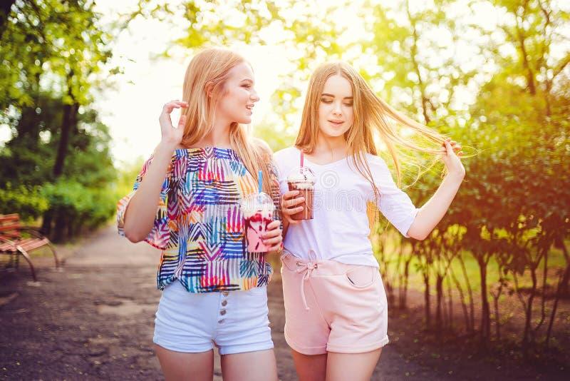 In tienervrouwen met dranken stock afbeeldingen
