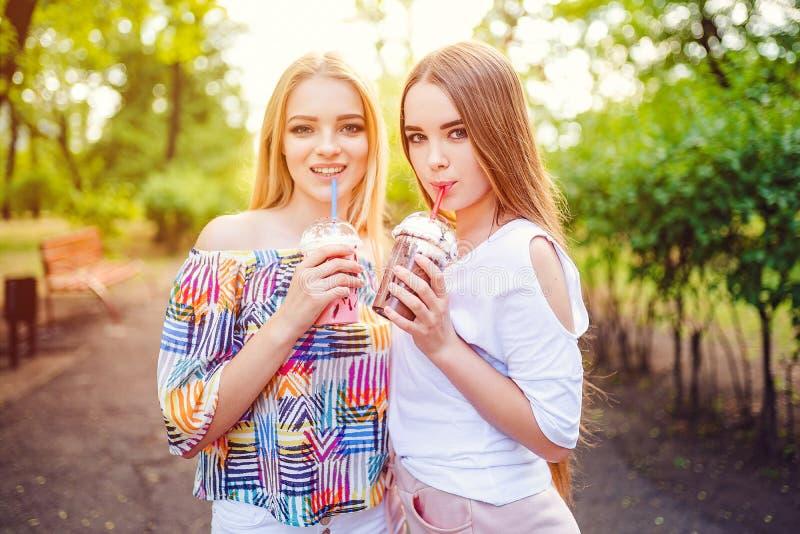 In tienervrouwen met dranken stock fotografie