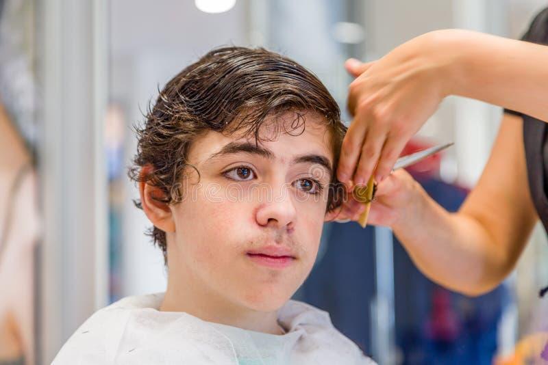 Tienerzitting bij de kappersalon voor een kapsel stock foto