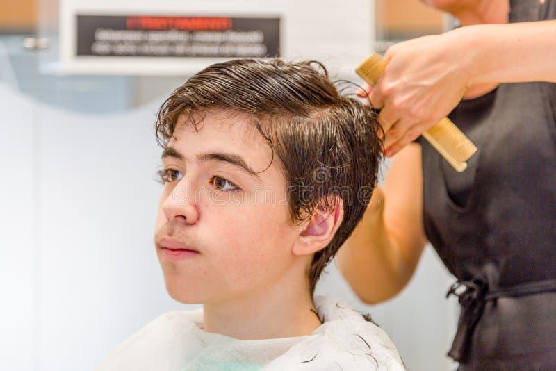 Tienerzitting bij de kappersalon voor een kapsel royalty-vrije stock afbeelding