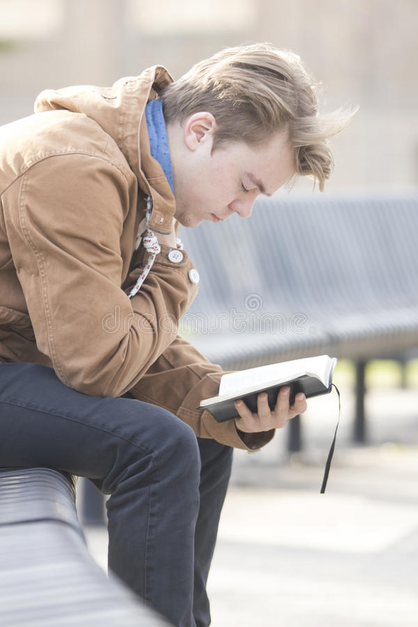 Tienerzitting op bank en het bidden stock foto's