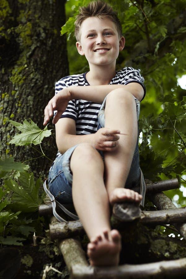 Tienerzitting op een houten ladder, het glimlachen royalty-vrije stock afbeelding