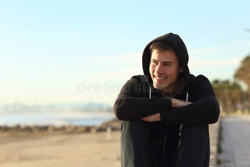 Tienerzitting op het strand die weg eruit zien stock foto's