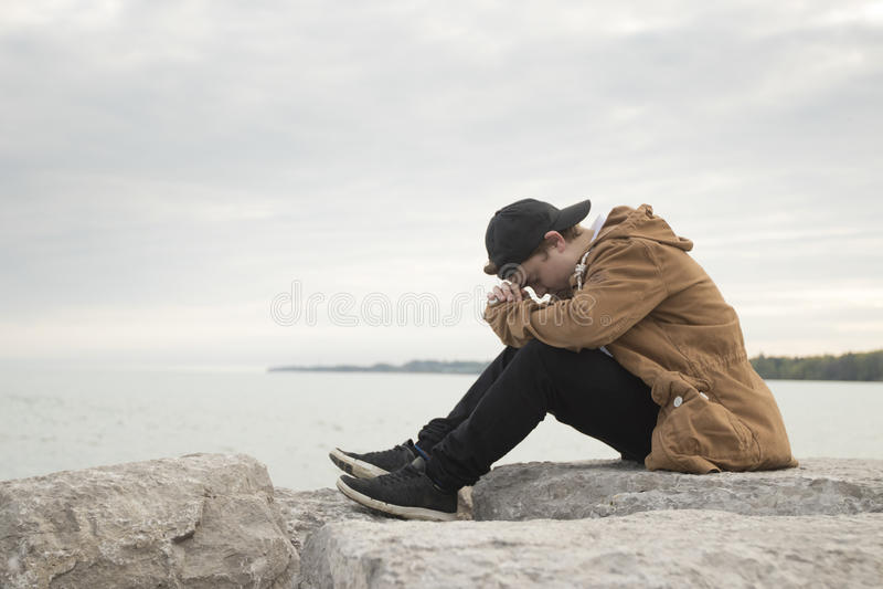 Tienerzitting op rotsen en het bidden stock fotografie
